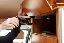 Det smarta skåpet ovanför garderoben vid ingången rymmer ett stativ för en platt tv-apparat.