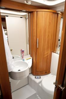 Vägg och handfat går att fälla ut och skyddar då hörnskåp och toa vid duschning.
