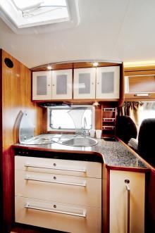 Köksdelen är rymlig med en bra avställningsyta ovanpå det utdragbara skafferiet till höger. En liten skulburk finns infälld längst bort i bänken. Högt uppe till vänster syns utblåset för klimatanläggningen som är extra utrustning.