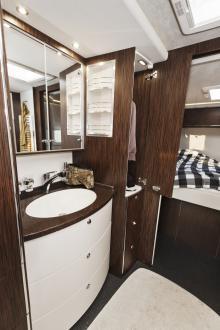 Samma bruna skiva i badrummet som i köket. Matchas med pärlemorvita skåpfronter och snickerier i wengeutförande.