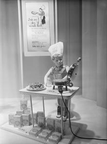 """NK:s skyltfönster, 1950. En liten pojkskyltdocka, i kockmössa med NK Livs logotyp och kockkläder, lagar våfflor. På ett anslag på väggen bakom honom står det: """"Inte ens den minste kock kan misslyckas med våfflorna när man använder VATO färdigblandade ingredienser som bara behöver tillsättas med vatten! SYLTEN har mamma redan köpt på NK-livs förstås!"""" Foto: Nordiska Kompaniet, ©Nordiska museet"""