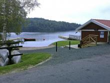 Bastu, kanoter, bryggor och strand vid sjön Bunn för ställplatsens besökare.