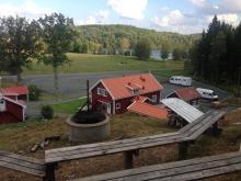 Grillplats med utsikt över ställplatsen och sjön i bakgrunden.