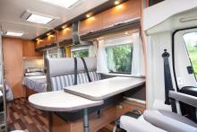 Äta. Matbordet är vägghängt och har en förlängningsskiva.  Fräscha och neutrala textilier. Köket är placerat bakom soffan.