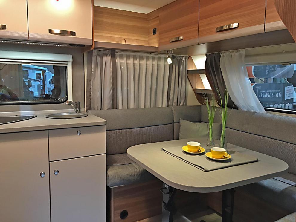 Enkla men funktionella möbler utan lyx. Öppna hyllor blandas med överskåp med luckor. Rätt liten u-soffa för vagnens storlek.
