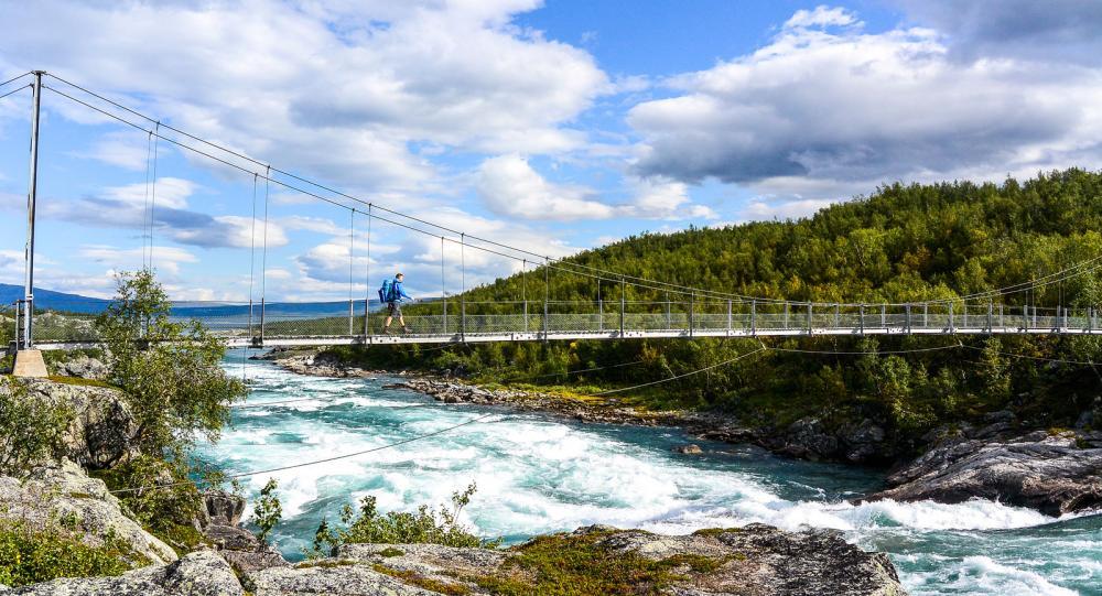Hängbron över Vuojatädno, älven som utgör den västra gränsen för Stora Sjöfallets nationalpark och är en av fjällvärldens större oreglerade vattendrag. Foto: Mats Jacobsson