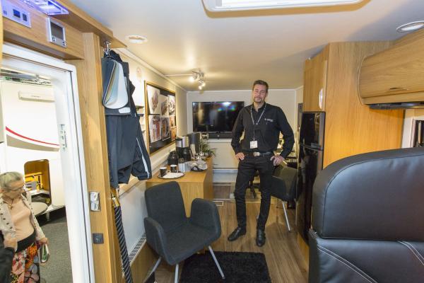 Per Grödevik visar stolt upp Nordics husbil med kontorsmiljön i centrum