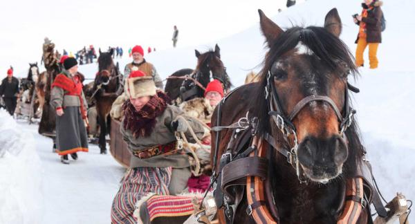 Närmare 90 ekipage med hästdragna slädar kör in på torget i en långrad.