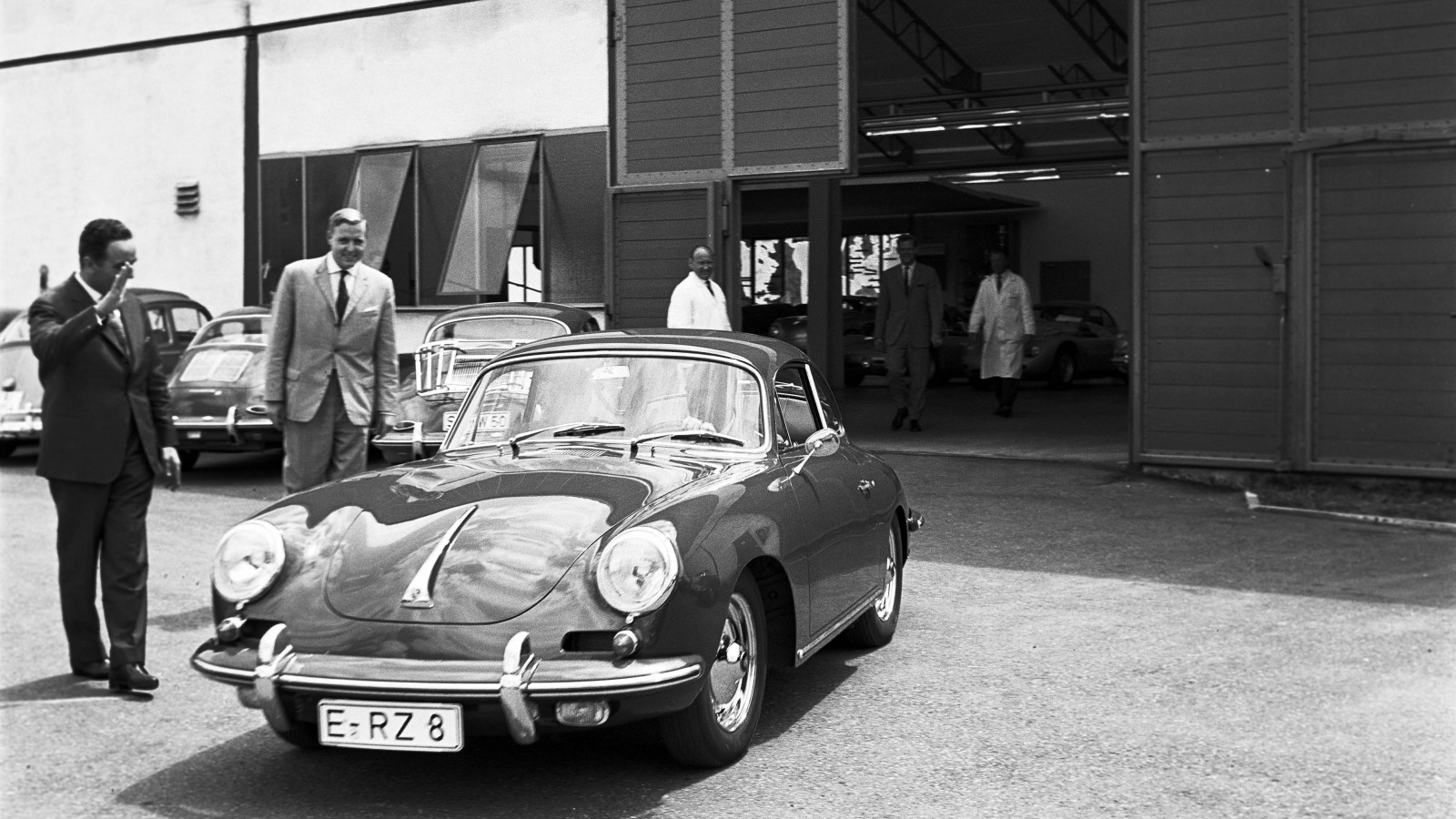 Porschemedarbetarna Harald Wagner och Alfried Krupp vinkar adjö åt den nyblivna 356 B-ägaren.