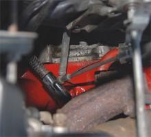 Längst ned i röran ser vi källan till gnället. Armen från gaspedalen gick mot motorvärmarens element där en plastisolering frambringade ljudet som hördes tydligt inne i bilen.