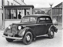 Det är år 1949 och vid vakten till GM:s stora anläggning i Hammarbyhamnen står den första Opel Olympia som kom till Sverige efter Andra Världskriget. Tekniskt skiljer den sig från förkrigaren genom skruvfjädrar fram i stället för den oljeinkapslade Dubonnetfjädringen.