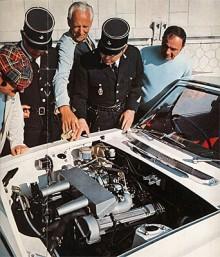 En svårtolkad broschyrbild! Fem personer, varav två franska poliser, studerar motorn. Mannen med Graham Hill-mustasch och förskräcklig keps är förmodligen den engelske bilägaren. Har han åkt fast för fortkörning? Men vem är mannen i verkmästarrock som pekar så sakkunnigt med cigaretten? Jobbar han på den lokala Triumphverkstaden? Den femte mannen är nog bara nyfiken, en innocent bystander.