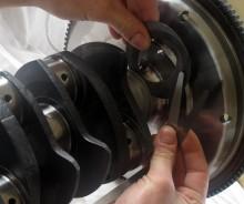 Hur mycket vevaxeln tillåts vandra fram och tillbaka i motorblocket begränsas av en fläns på lagret längst fram. Genom att ta bort eller lägga till shims mellan lager och svänghjul passar man in rätt mått. Det heter axialspel och är för övrigt ett utmärkt sätt att kontrollera en folkamotors kondition: Ta ett stöddigt tag i den nedre remskivan och rucka den fram och tillbaka. Om du hör ljudliga klonk är motorn sannolikt färdig för renovering.
