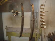 Hänger upp rader med framvagnsdelar i ståltråd för lackering