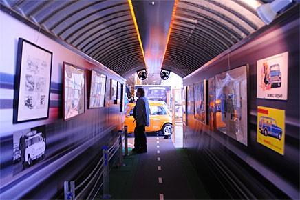 En tunnel fylld med reklambilder leder besökaren in i utställningen.