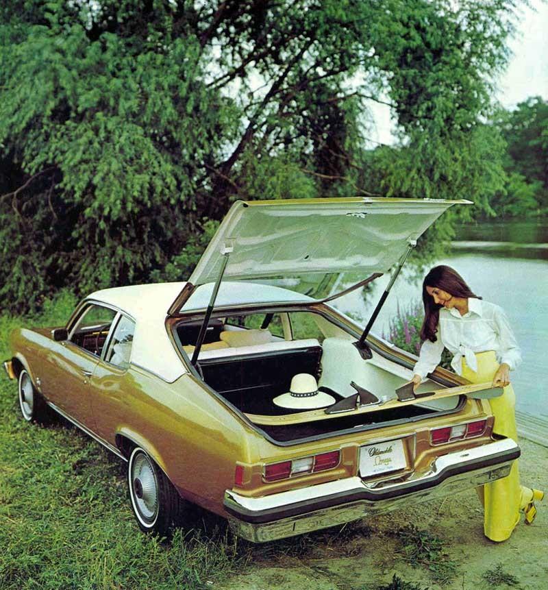 En wakeboard får ledigt plats i Oldsmobile Omega hatchback, men nog ser hon väl inte riktigt klädd ut för sådana vattenäventyr?