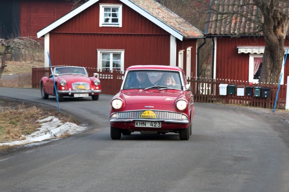 Röda engelska vagnar bland röda svenska stugor. Anglia och MGA.