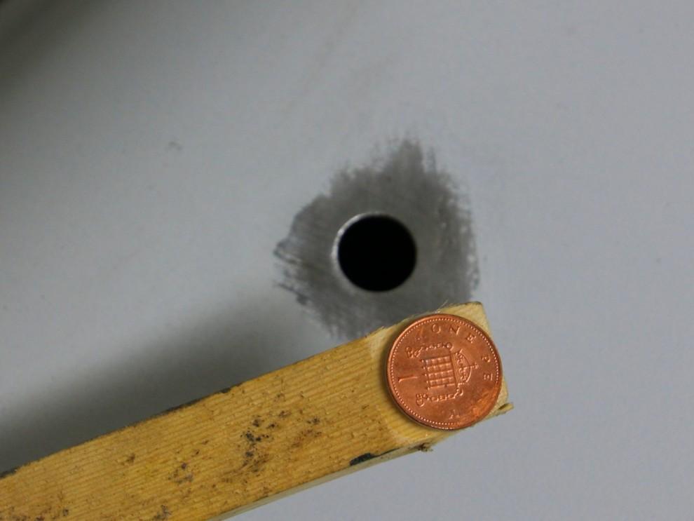 På skärmen har det en gång suttit en spegel, en misstänkt bula där avslöjade att det lagts igen med plastic padding och lite klet... Nu skall det bli riktigt denna gången så hålet skall svetsas igen. Tipset är att lägga i den nya biten och ha ett mothåll av koppar under. Nu är det lite svårt att komma åt här så då limmar jag fast en penny på en pinne och sticker in i skärmen.