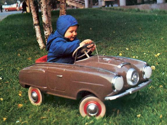 Glad ung sojvetmedborgare med sin nya fina trampbil från AZLK. Den här modellen är misstänkt lik en Studebaker