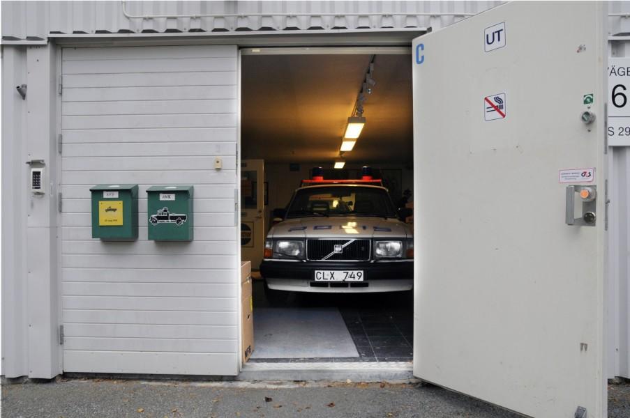Tittut! Jag är den moderna öppna polisen med nyskapande typsnitt! Volvo 240 med så kallad hockeyklubbsdekor kikar ut ur dörren på det som var Polistekniska Museet.