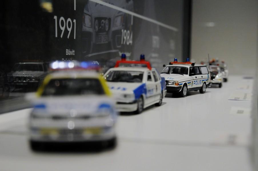 Modellbilar på rad visar utvecklingen av målningen på polisbilar.