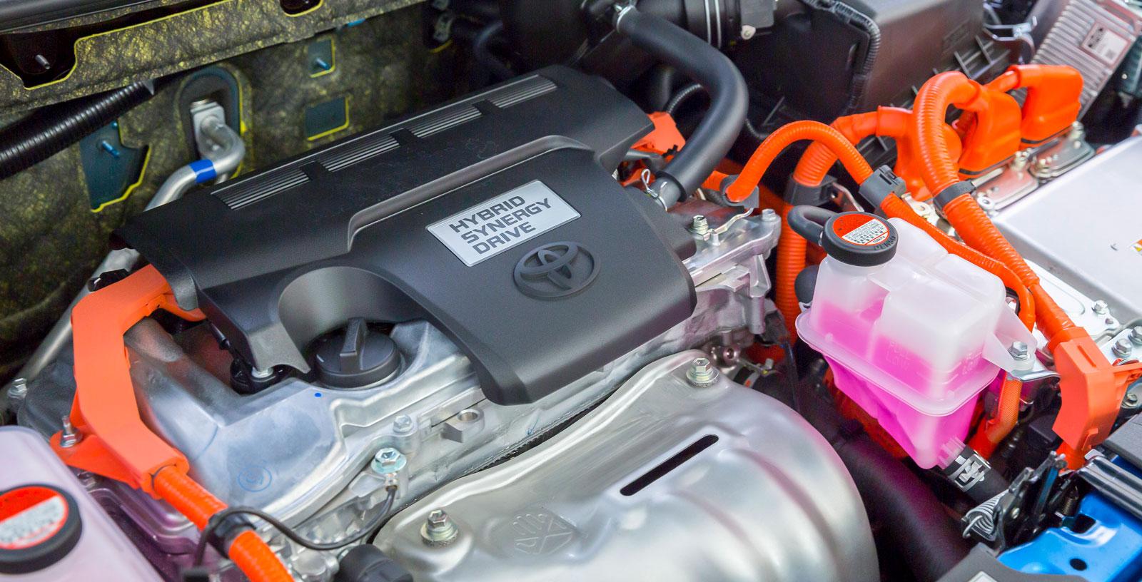 Toyotas färgglada motorrum inrymmer både bensin- och elmotor. Effekten är testets högsta och bilen har riktigt raska fartresurser när den pressas en smula – till priset av ett oskönt, råmande motorljud. På tomgång är motorkombinationen desto mer tystlåten.