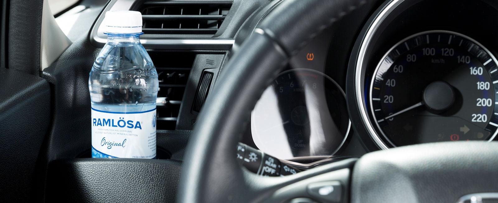 Till vänster om ratten sitter ett smart fack med utsökt placering för flaskor eller telefoner.