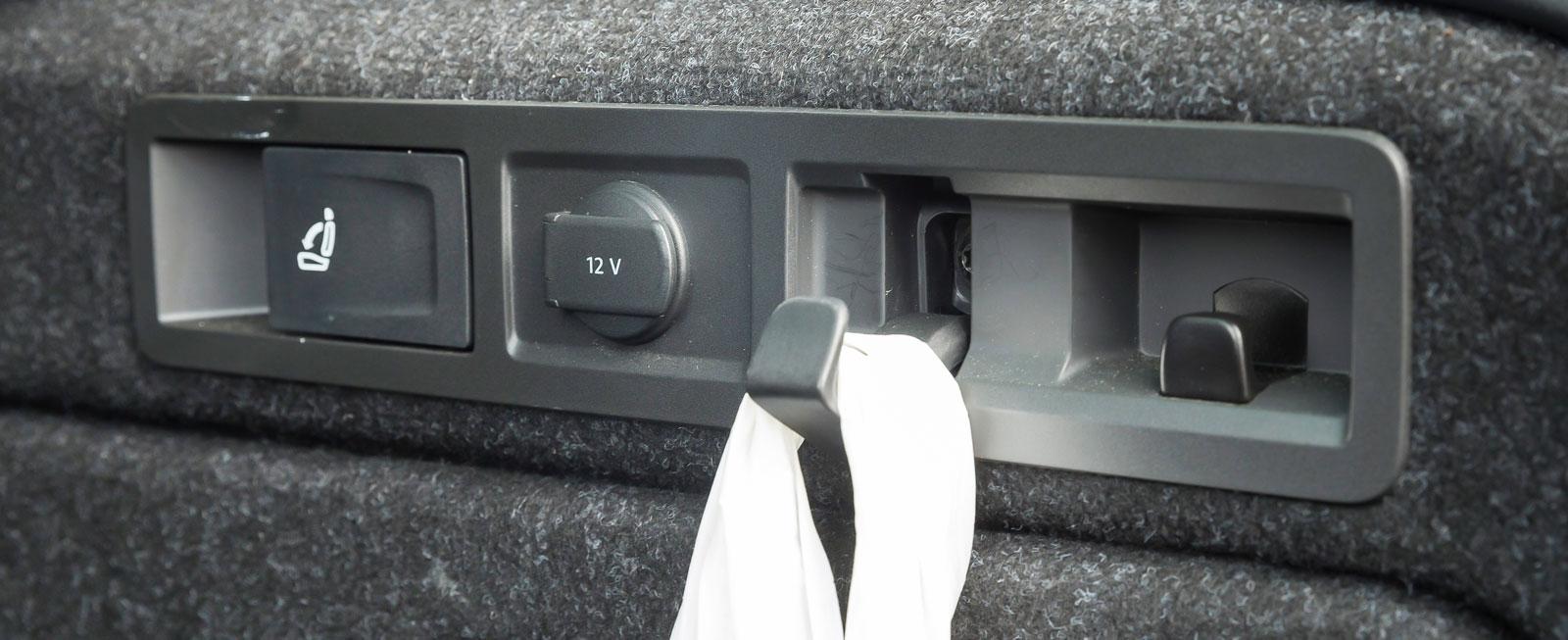 Kasskrok (totalt finns fyra), 12 V-uttag och fällningshandtag för ryggstöden sitter prydligt samlade på sidan i lastutrymmet.