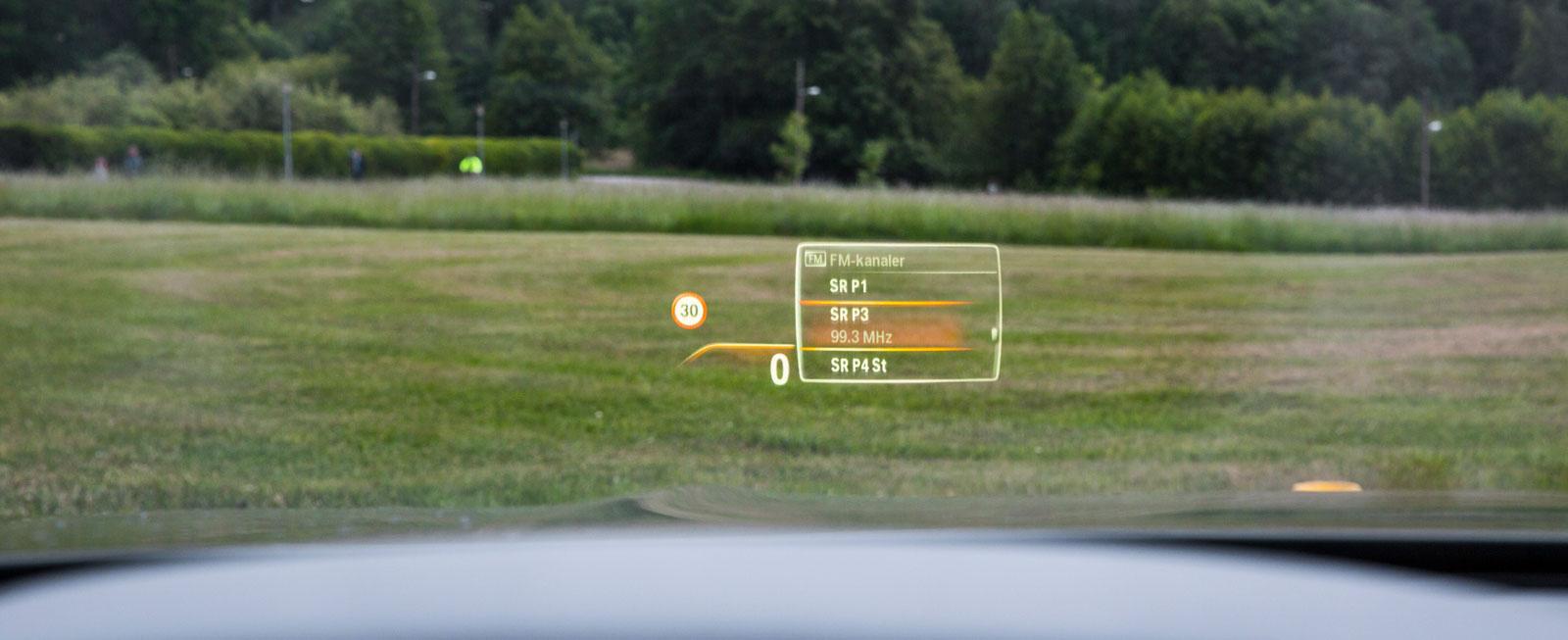 Stor head up-display. Via rattknapparna kommer radiolistan upp på vindrutan när man letar nästa station.