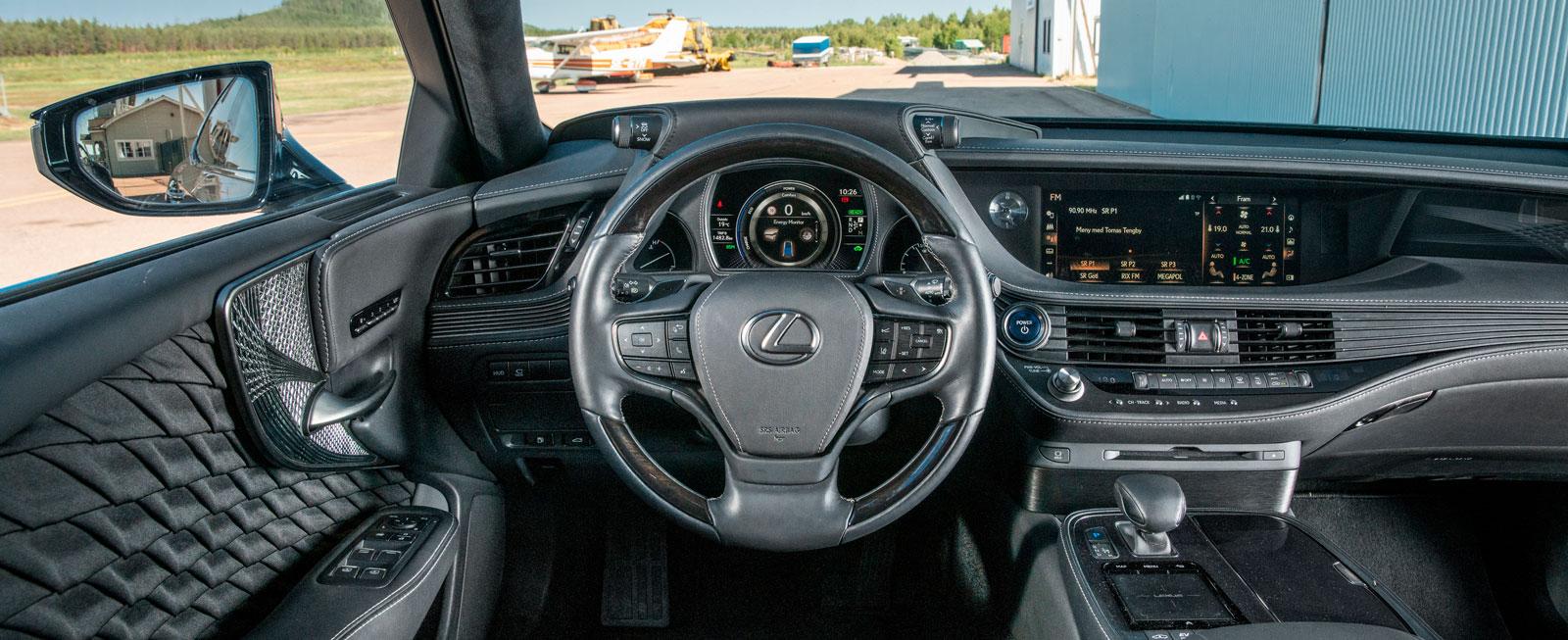 Det är ganska mörkt och dystert på Lexus förarplats. Knapparna i ratten är närmast osynliga i dagsljus och mediesystemets pekplatta kräver träning.