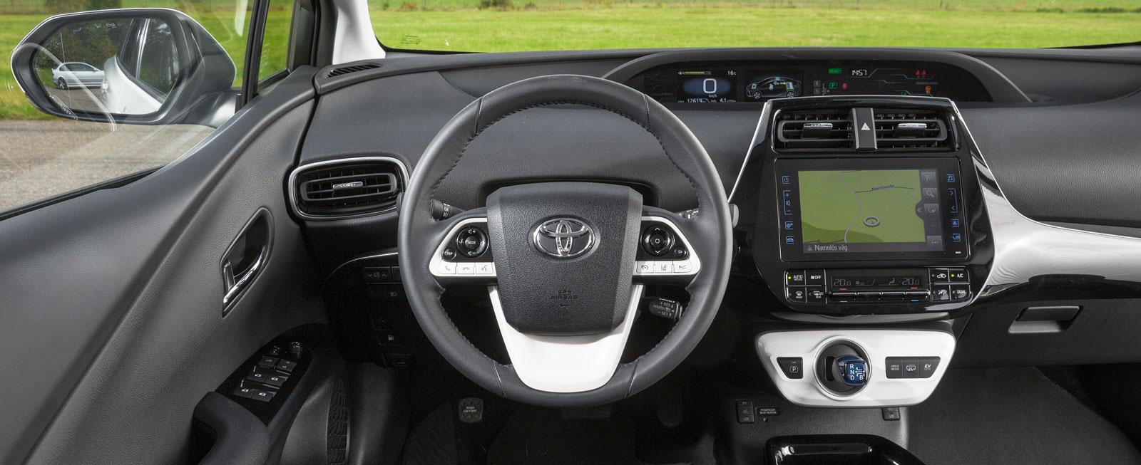 Ovanligt låg sittställning för att vara en Prius och sköna framstolar. Centralt placerade mätare ger sämre avläsbarhet.