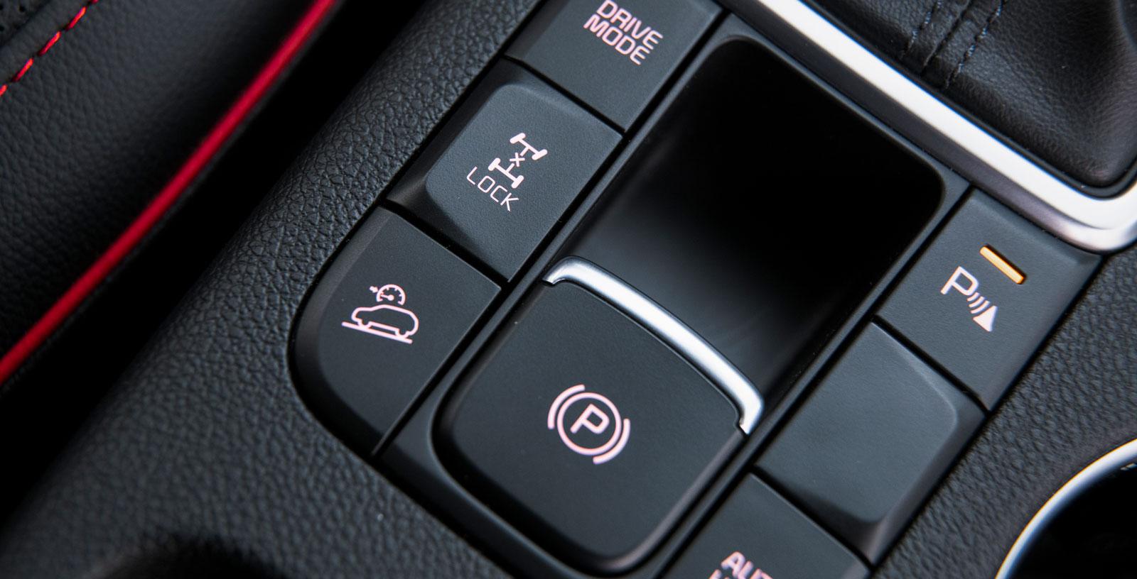 """""""Lock"""" låser fyrhjulsdriften elektroniskt till 50/50-drivning. Knappen under används för att i utförslöpor hålla bilen i en konstant, låg hastighet."""