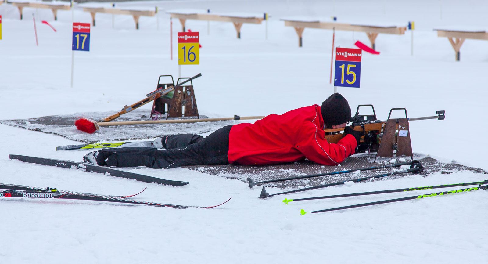 Obekväm ställning i skidskyttet, liggande med skidorna spretande åt olika håll. Och pricktavlorna 50 meter bort.