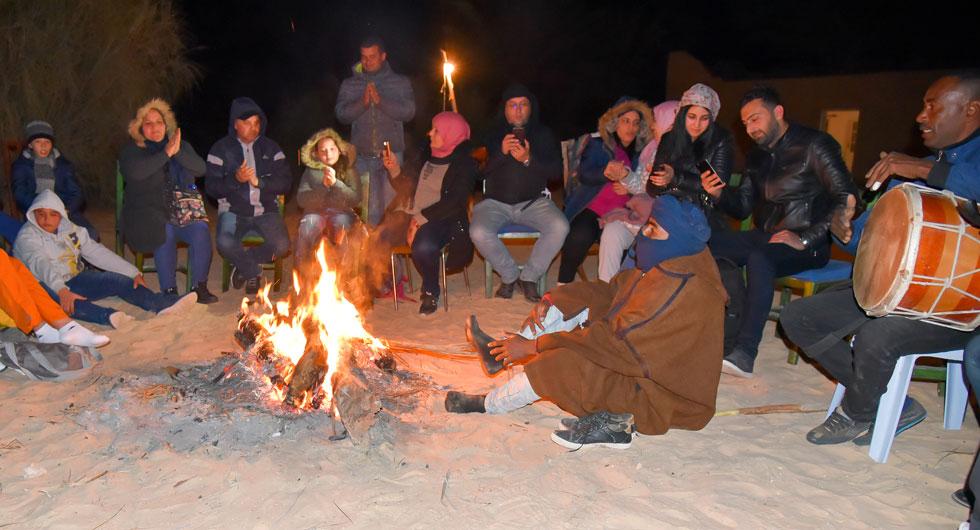 Om kvällen blir öknen kall. De som övernattar i oasen samlas och värmer sig vid elden.