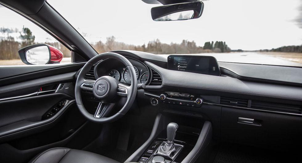 I Mazda 3 sitter man lågt och omsluten av höga karossidor. Reglagen som styr klimatanläggningen är inte så tydliga som man kan önska.