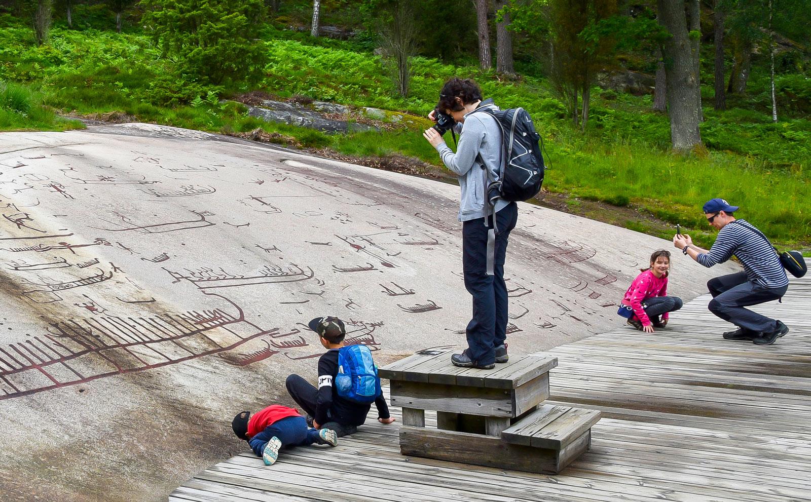 Familjen Gradalski studerar bilderna på Vitlyckehällen som berättar om livet vid havet under bronsålderstid.