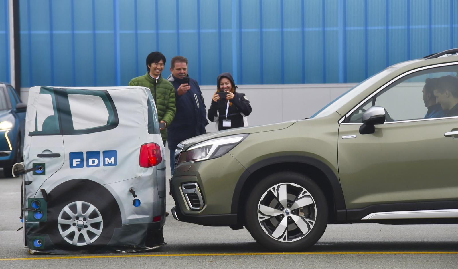 Nöjda representanter från Subaru ser på när Forester nödbromsar från 85 km/tim och precis undviker en krock. Bäst i test jämte BMW 1-serie.