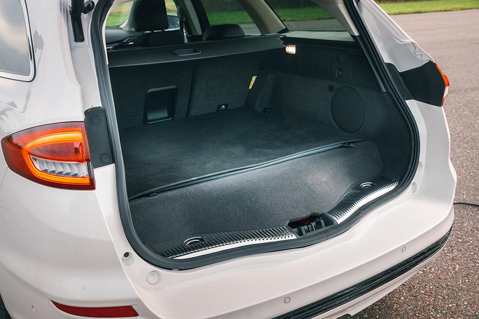FORD: Med fällt baksäte blir det möjligt att stuva in 1508 liter gods. Kraftiga lastsäkringsöglor uppskattas alltid, men varför så liten genomlastningslucka? Djup och repkänslig stötfångare, den extra mattan kan vikas ut och skydda. Högtalaren till höger i bagaget har en utsatt position.