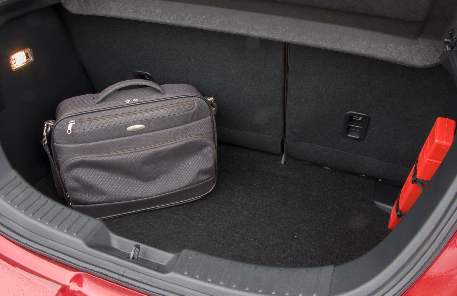 """Kort bakparti med futtigt bagageutrymme av billigt utförande. Golvet består av en särdeles sladdrig skiva """"wellplast""""."""