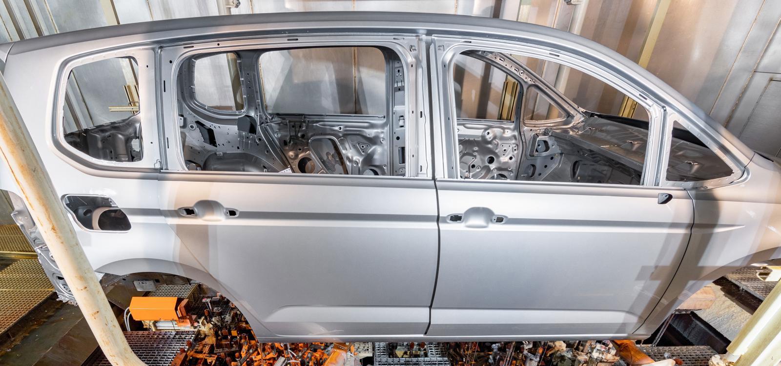 En Touran sänks ner på munstycken som fyller tröskellådorna med vax. Foto: Volkswagen
