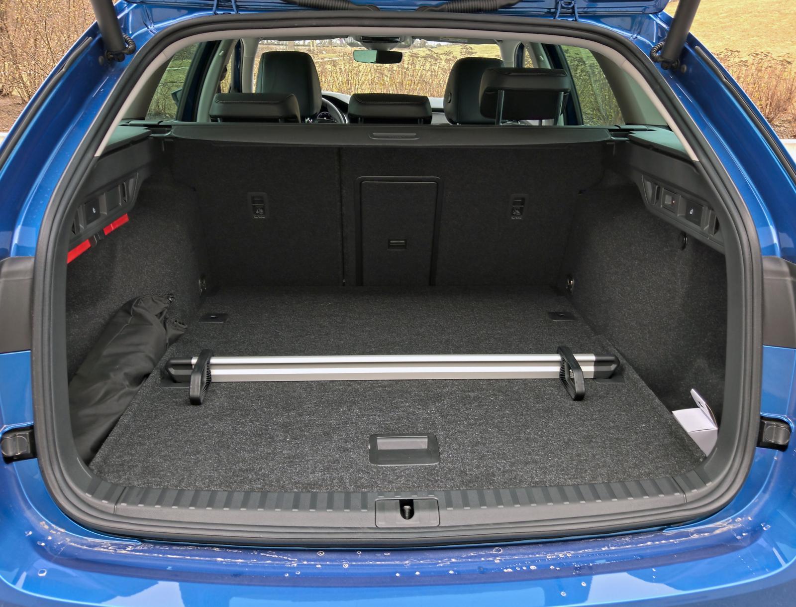 Bagagerumsdelaren kan likt insynsskyddet stuvas under det dubbla golvet. Påse till vänster = lastnät.