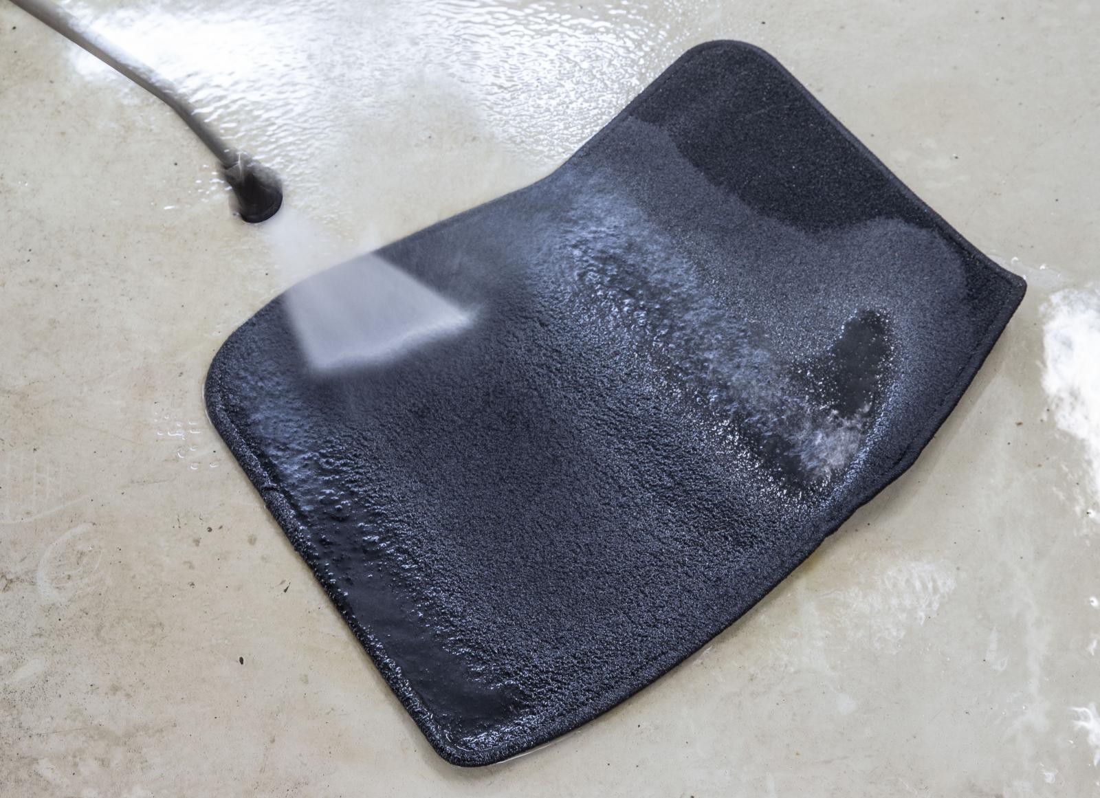 Högtryckstvätten hålls på visst avstånd för att inte skada mattans struktur.