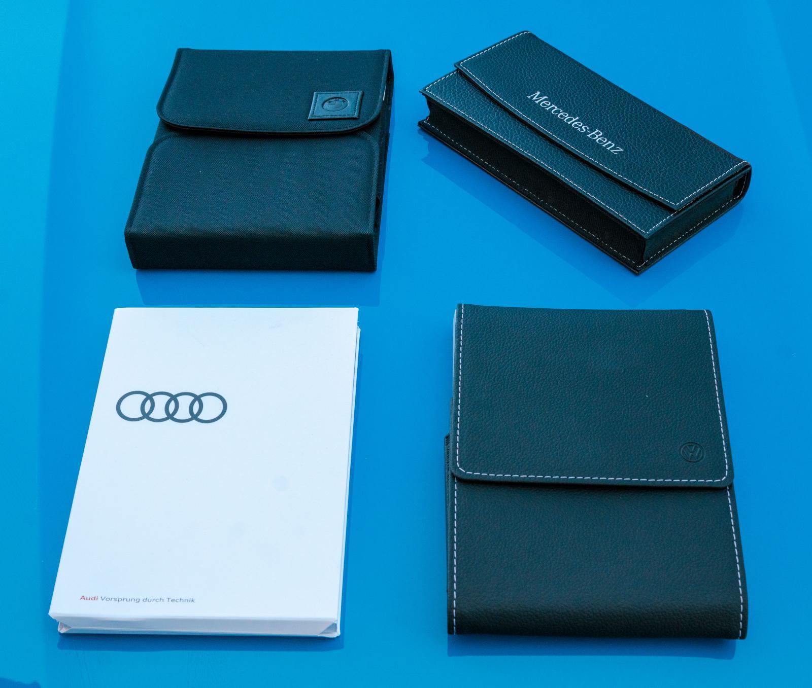 402 sidor BMW-manual (övre vänstra) levereras i textilfodral. Audis instruktionsbok huserar i ett mer miljövänligt pappersfodral. Mercedes och VW konstläderfodral har kontrastsömmar – påkostat.