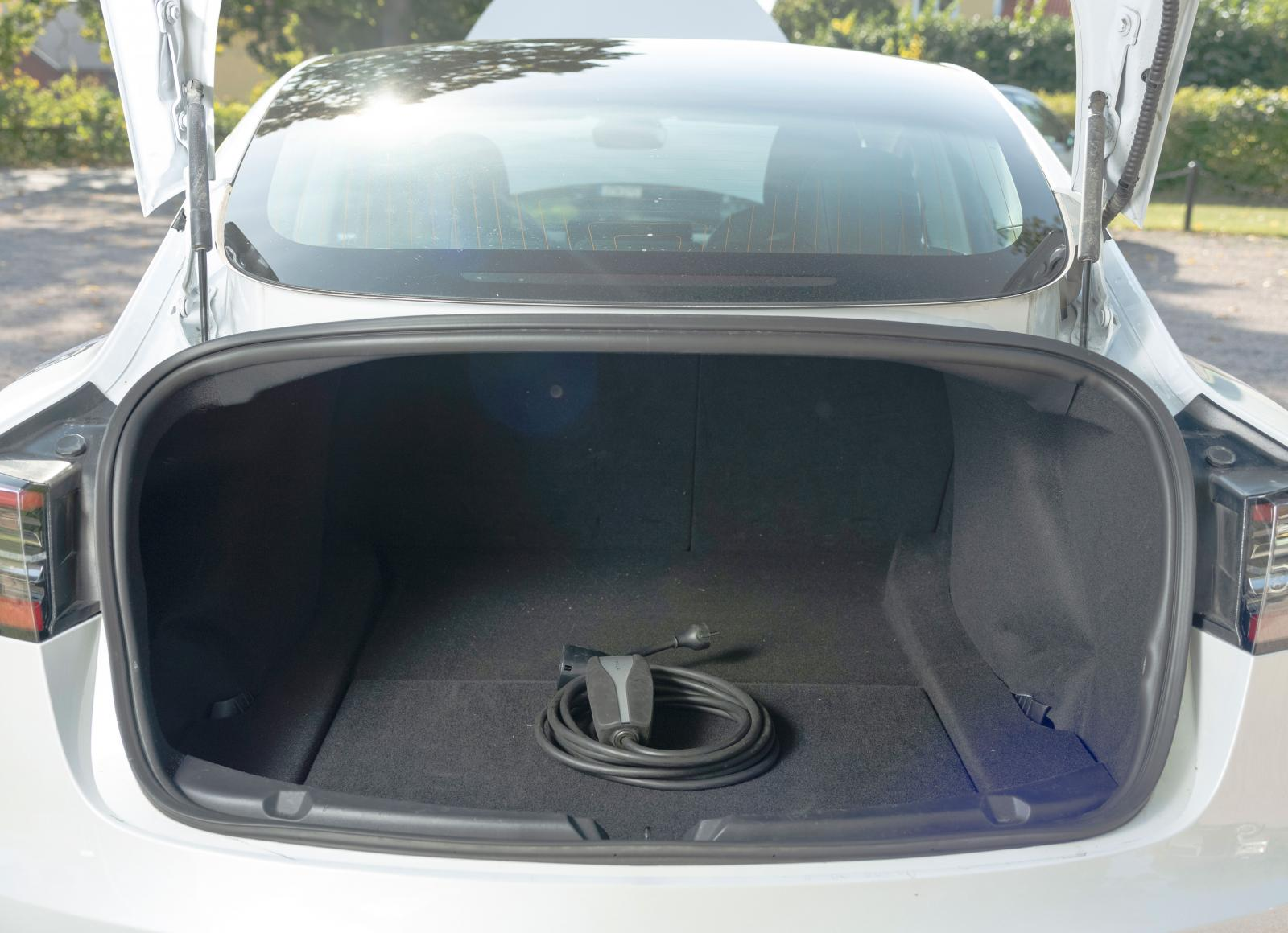 Man får sträcka sig rejält för att nå längst in i Teslas bagageutrymme. Eller också får man fälla de bakre ryggstöden från kupén. Lastöglor saknas men under golvet finns fack för sladdar och avtagbar dragkrok.