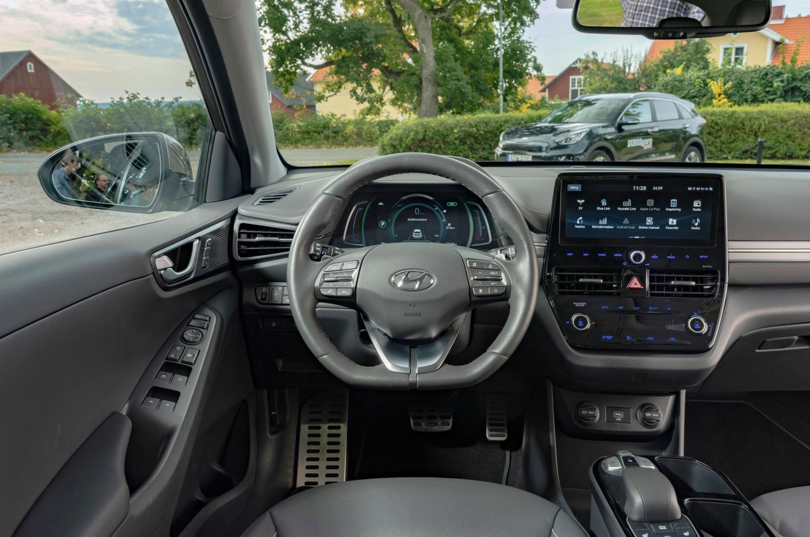 Hyundai: Nedtonat, nästan som ett svartvitt foto, utmärkt finish och logisk skötsel utmärker Ioniqs förarplats. Växelväljare med knappar mellan stolarna.