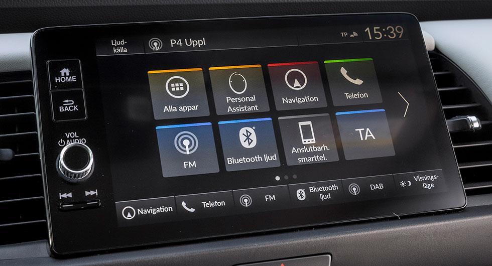 Till vänster om skärmen fysiska knappar och volymvred. I nederkant av skärmen touchknappar till ofta använda funktioner.