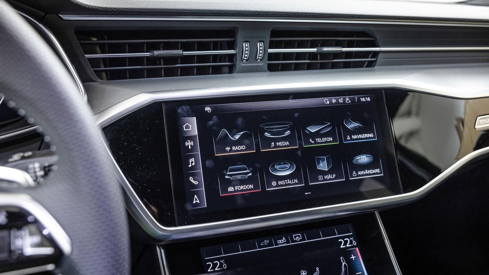 """Audi: Elegant inbyggd skärm med mycket tydlig grafik och förhållandevis lättpekade val – men det hela kräver viss övning innan kommandona """"sitter"""". Klimatanläggning och skrivplatta finns i den nedre skärmen."""