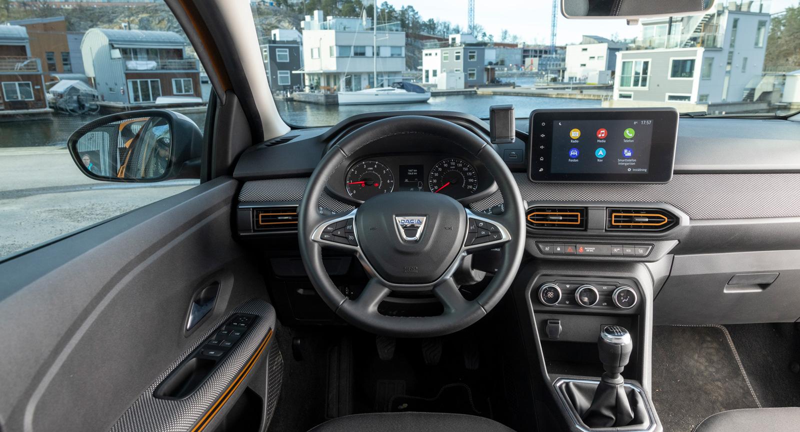 Dacia: Instrumentpanelen är delvis textilklädd, det känns påkostat. Orange accenter på dörrhandtag och friskluftsutblås särskiljer Stepway. Hal ratt.