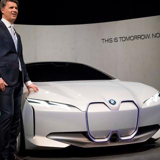 BMW:s chef Harald Krüger poserar tillsammans med ett koncept på kommande elbilen i4 i samband med biltillverkarens årliga presskonferens.