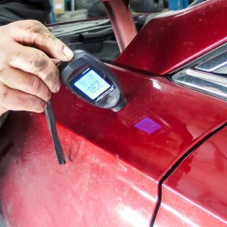 Med en my-mätare kan man enkelt konstatera om bilen är omlackad. Lacken är ofta dubbelt så tjock på de ställen som reparerats. På bilden visar mätaren 230 my, mot normala 100–120 my.